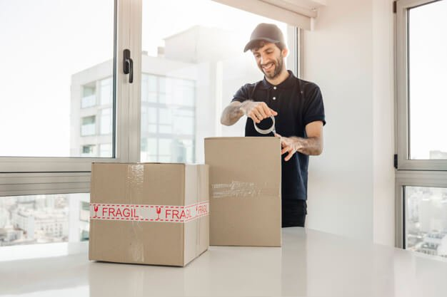 delivery-man-taping-up-cardboard-boxes_23-2147862247